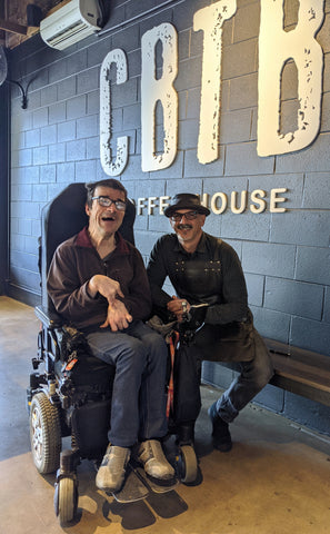 DrDazz, in his electric wheelchair, sitting next Vincent, who is wearing a leather rimmed hat. They next to a black painted brick inside wall with the letters CBTB painted on it.