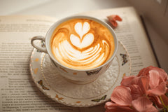 Cup of coffee with latte art sitting on an open book