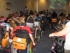 Picture of ISAAC Conference session from Barcelona in 2010 with many AAC users in wheelchairs