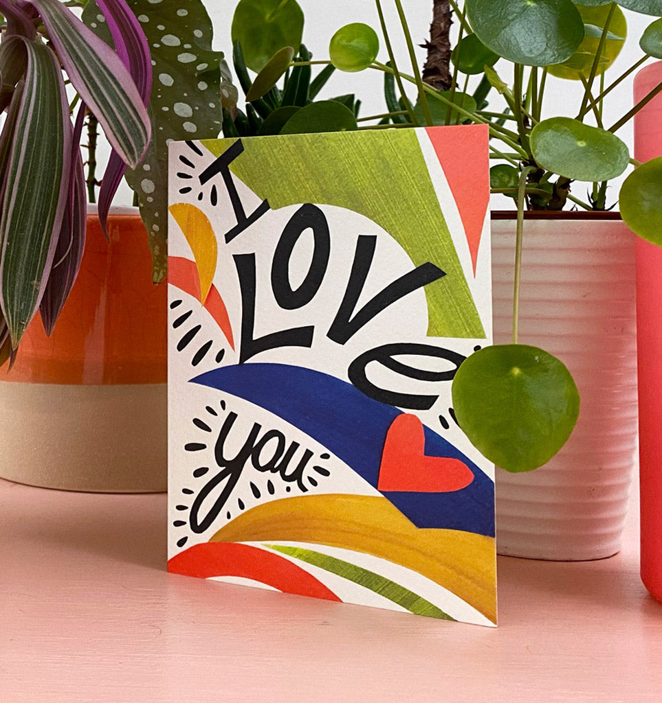 Collaged card in green, orange, blue an yellow. I Love you is written in a hand written bold style. Lifestyle photo with plants on background.
