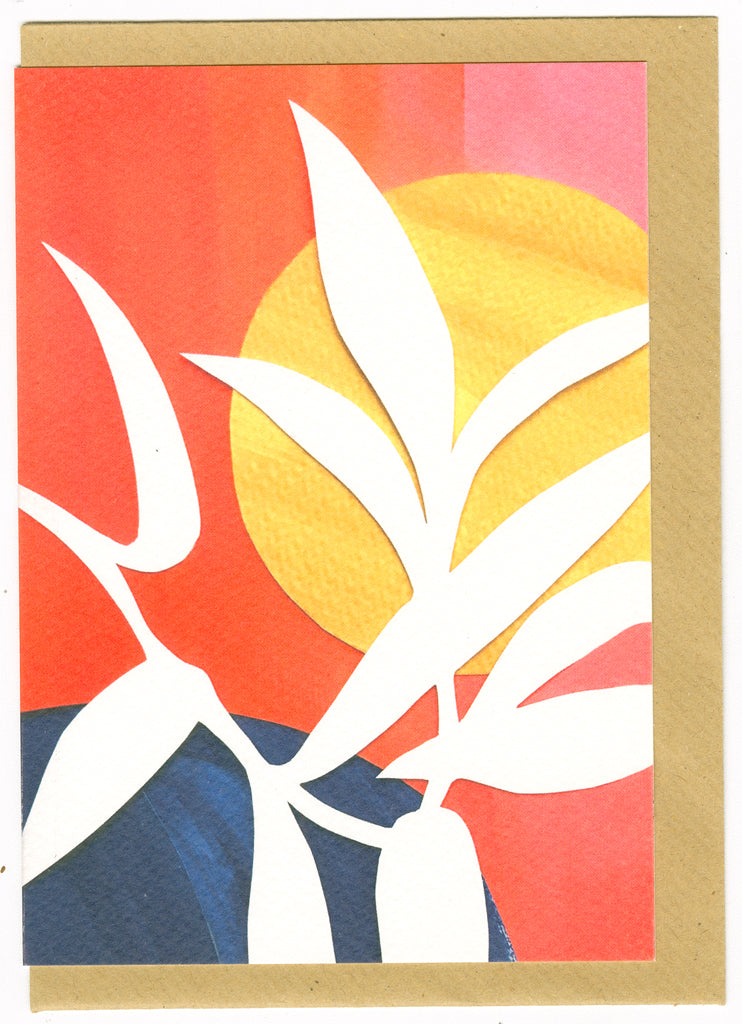 Close up of sunrise card, ecru silhouette of plant with yellow sun in the background, and orangey/red tones behind that.
