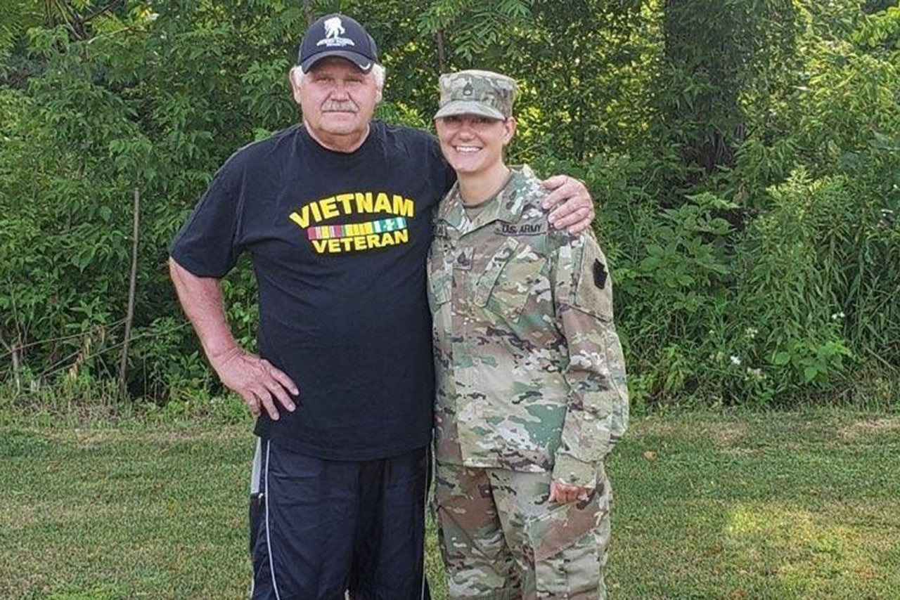 man standing with daugher in military uniform