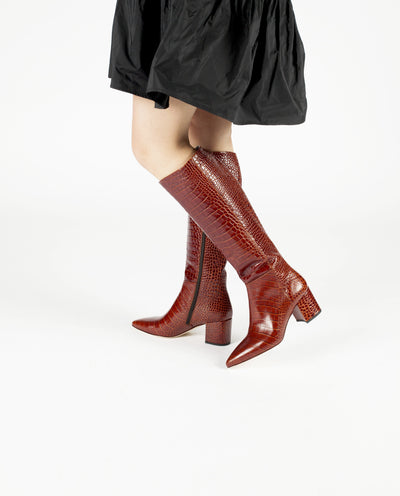 A red croc Italian leather knee high boot with a block heel and a pointed toe.