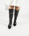 A black Italian leather knee that features a covered leather block heel and a pointed toe.