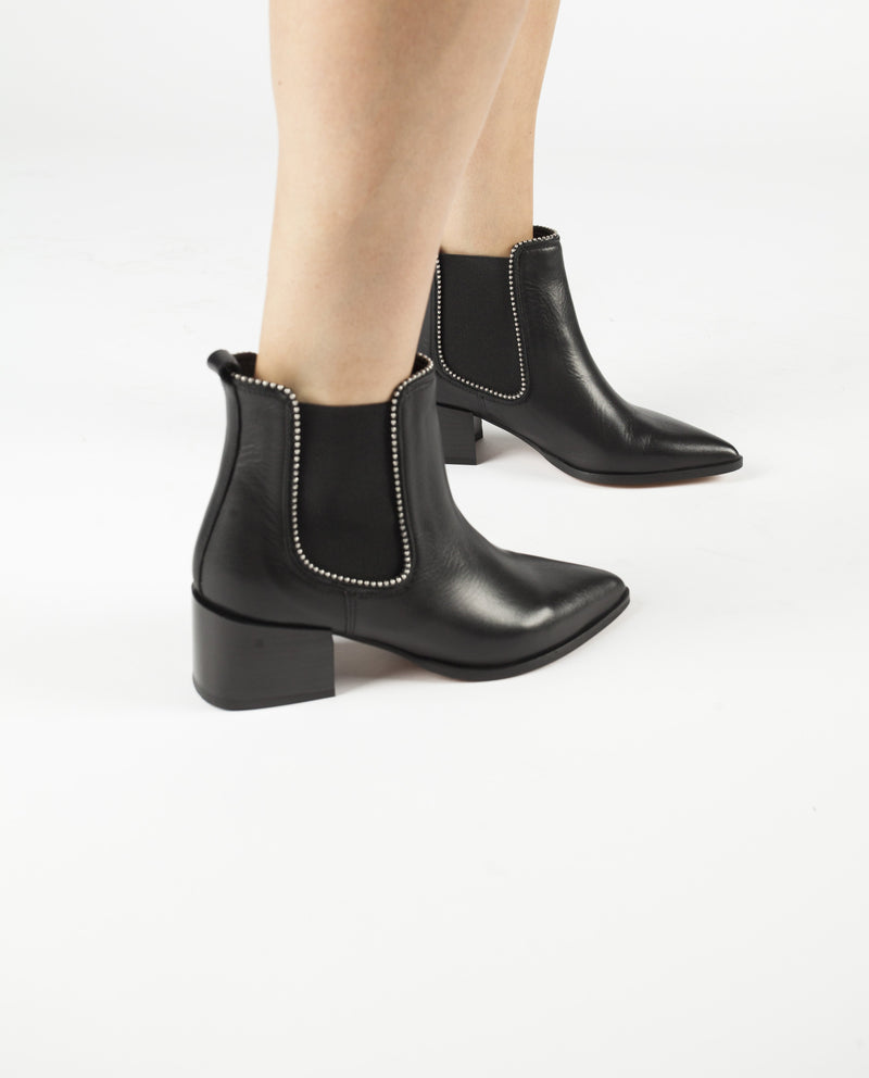 A black leather ankle boot featuring elastic side gussets, silver detailing, a block heel and a pointed toe. Made by Christian Di Riccio. This style runs true to size.