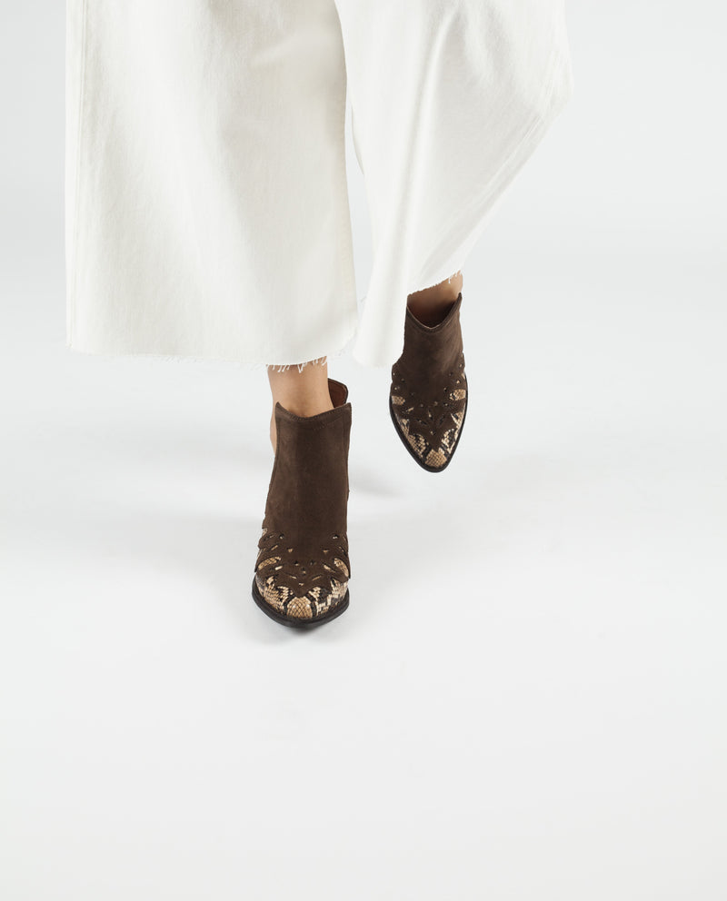 A brown suede and brown snake print Western style slip on ankle boot that features cut out sides, a block Cuban heel and a pointed toe by Jeffrey Campbell.