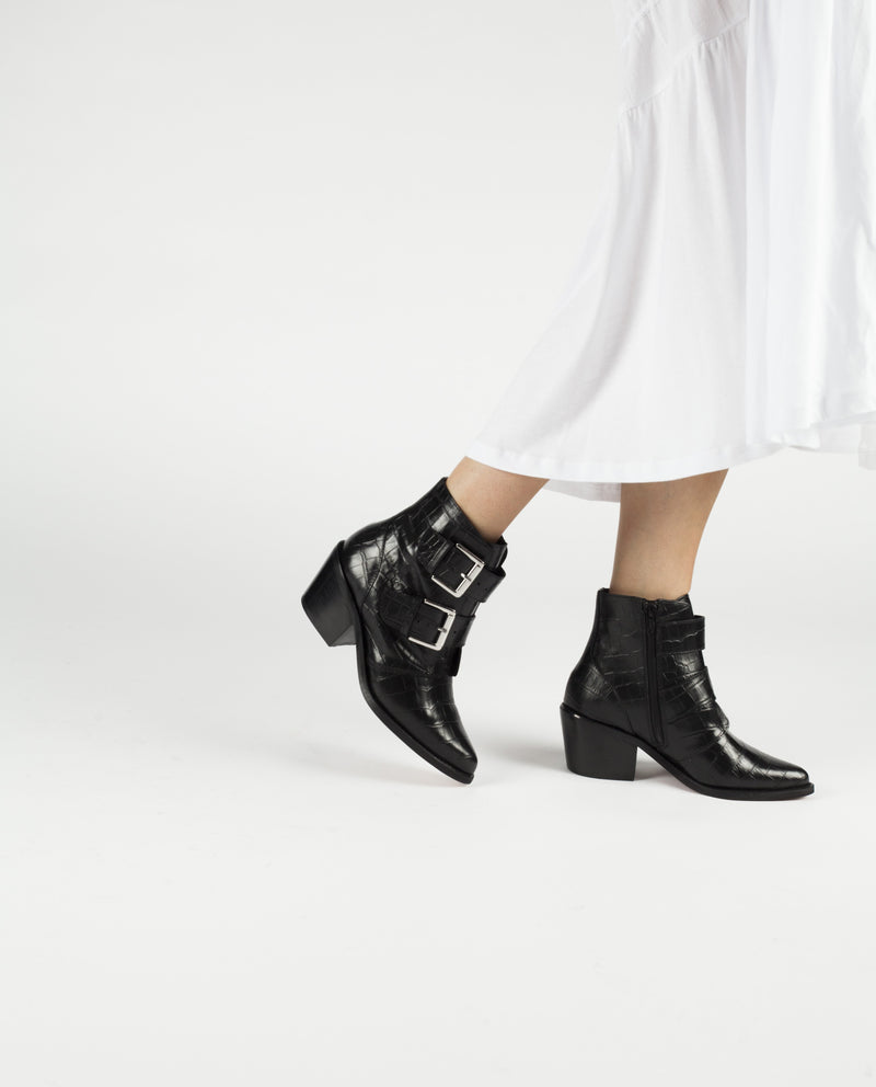 A black leather western style boot featuring silver buckle fastenings, a croc skin like finish, a block heel, and a pointed toe. Made by Christian Di Riccio. This style runs true to size.