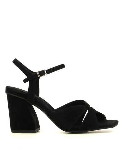 A black suede heeled sandal by Jeffrey Campbell. The 'Antique' features a cross over upper, an architectural heel and a square toe.