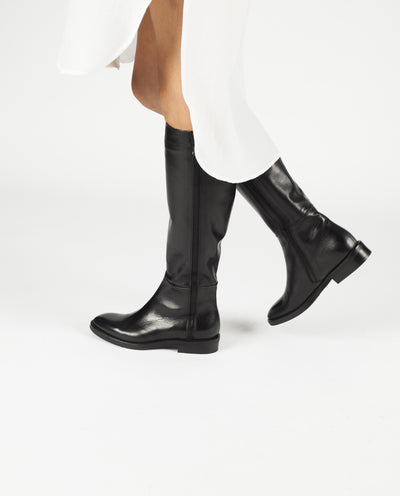 A flat black Italian leather knee high boot by Le Pepé. The 'B695962' has an inner zipper fastening and features a decorative zip on the outer, a short block heel and an almond shaped toe.