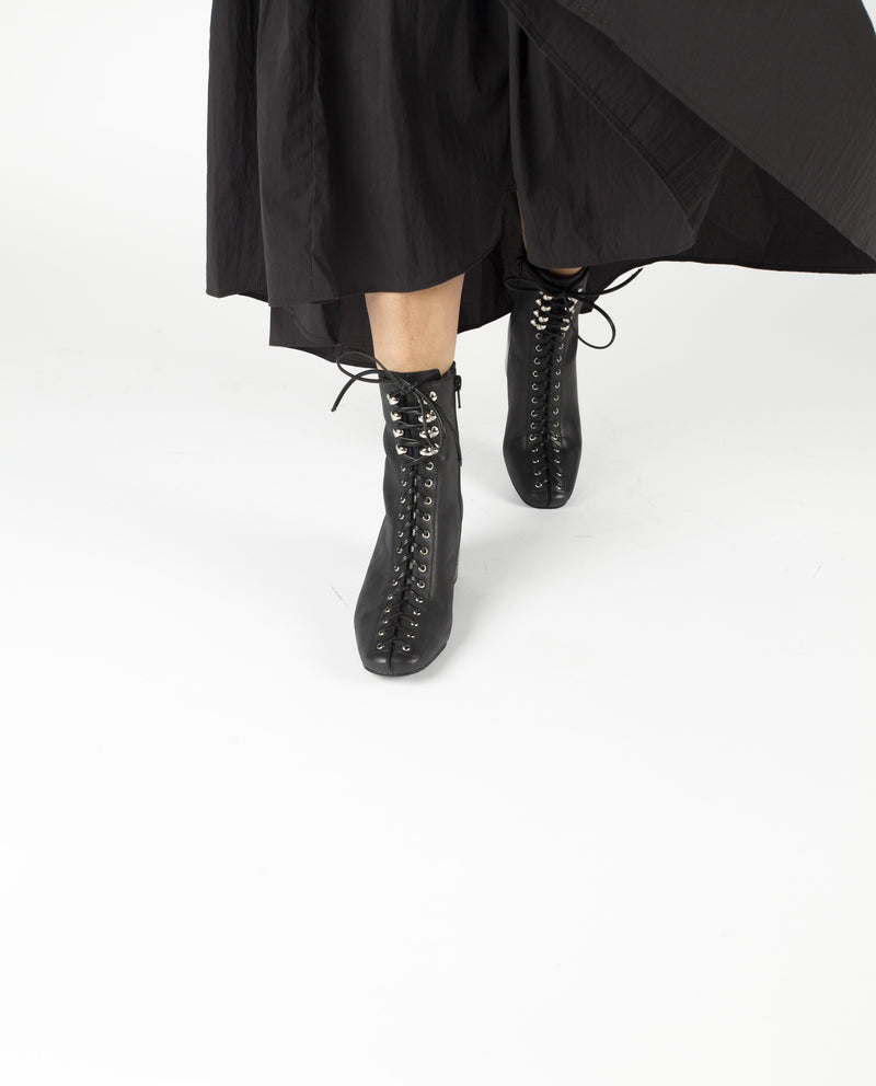 A black leather ankle boot that features laces from the tip of the toes to the top of the boot. This style also had zipper fastening and features a 6.5cm block heel and a soft square toe by Jeffrey Campbell.