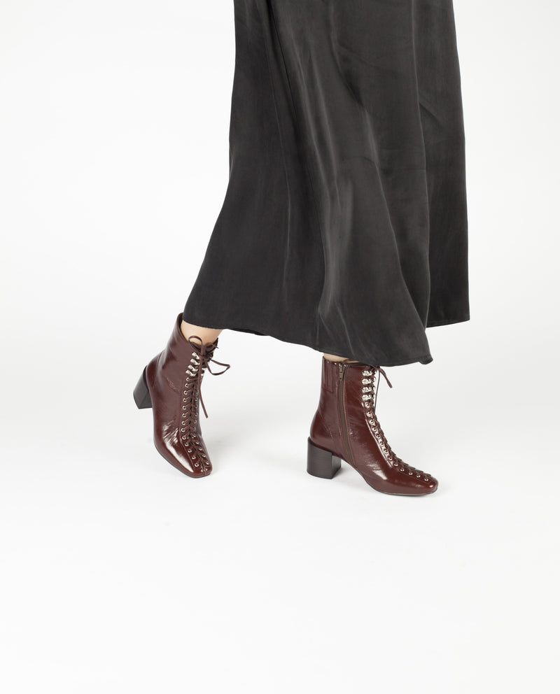A dark brown leather ankle boot that features laces from the tip of the toes to the top of the boot. This style also had zipper fastening and features a 6.5cm block heel and a soft square toe by Jeffrey Campbell.
