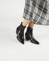 A black leather western style ankle boot by Elena Iachi. The 'E1565' Has zipper fastening and features a Cuban heel and a pointed toe.