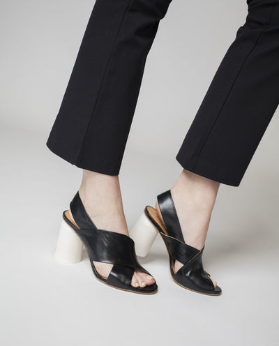 A black Italian made leather heeled sandal by Halmanera featuring cross over straps, a white cylindrical block heel and a round toe.