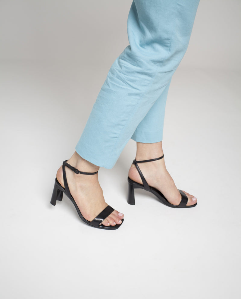 A black heeled sandal by Neo X. The 'Fancy' features a buckle fastening and a soft square toe.