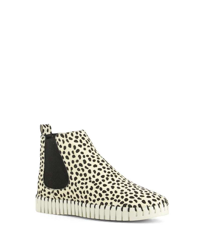 A white and black dot textured leather sneaker style Chelsea ankle boot that features a ribbed sneaker sole and a round toe by Django & Juliette,