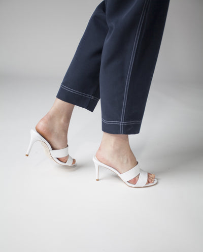 A white leather high heel sandal by Robert Robert. The 'Ondine' features a strappy upper, a stiletto heel, and a soft round toe.