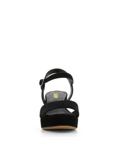 A black suede platform, block heeled sandal that features a silver buckle fastening and an open round toe by Zomp.