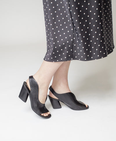 A black Italian leather sling back heel by Halmanera. Featuring a wave-cut upper detail, a block heel and a open round toe.