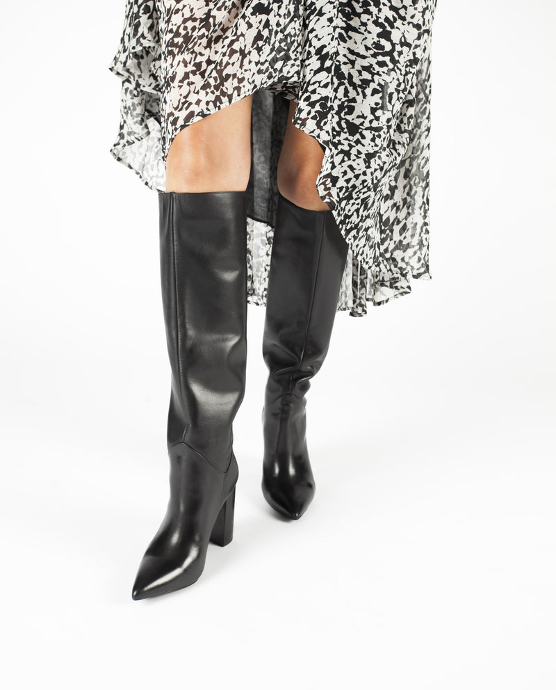A black leather knee high pull on boot that features a 9.5cm block heel and a pointed toe by Jeffrey Campbell.