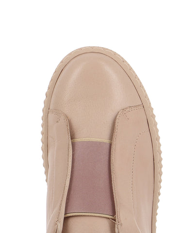 A dusty pink leather fashion sneaker that are slip-on style with a lace-free opening and features a reflective elasticated upper and a round toe by Django & Juliette.