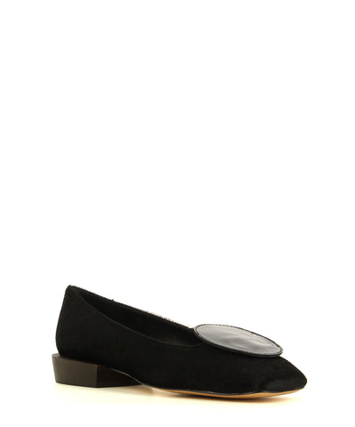 A 60's inspired black pony fur ballet flat by 2 Baia Vista. The 'Universe' features a black patent leather circle embellishment on the toe, a wooden block heel and a soft square toe.