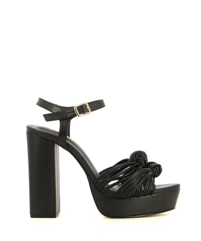 A black leather platform sandal featuring knotted toe straps, a buckle fastening and an almond toe. Made by ZOMP - this style runs true size.