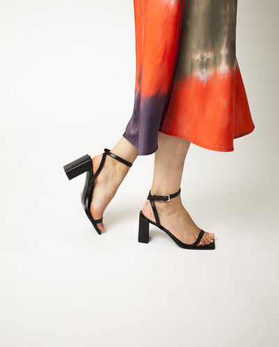 A black leather high heel sandal with ankle buckle fastening, a 8cm block heel and a square toe.