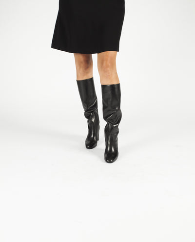 A black leather pull on knee high Italian leather boot by that features a concealed ankle gusset, a 8cm block heel and a rounded almond toe by Lorenzo Masiero. This style is true to size.