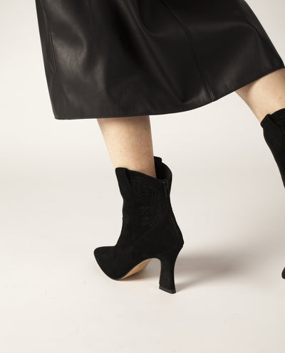 Black suede leather Western-style ankle boots that have a zipper fastening at the back and features a stitched Western design, an hourglass-shaped heel and a pointed toe by Zomp.