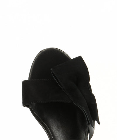 A black suede leather platform featuring an ankle strap with a buckle fastening, a knotted bow upper, a high platform heel and a round toe. Made by ZOMP - this style runs true to size.