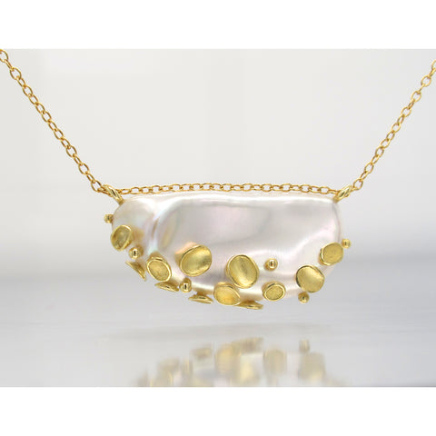 Shell pendant necklace in 18k yellow gold with a flattish white baroque freshwater pearl, $2,800; Barbara Heinrich; email info@barbaraheinrichstudio.com for purchase