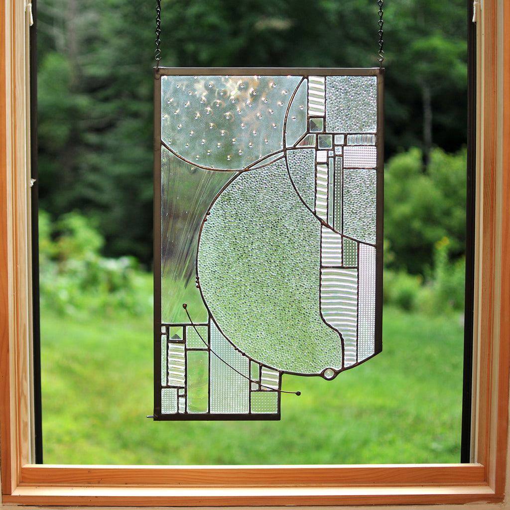 Stained glass panel with circular forms and clear textures made by Vermont artist Julia Brandis. Abstract.