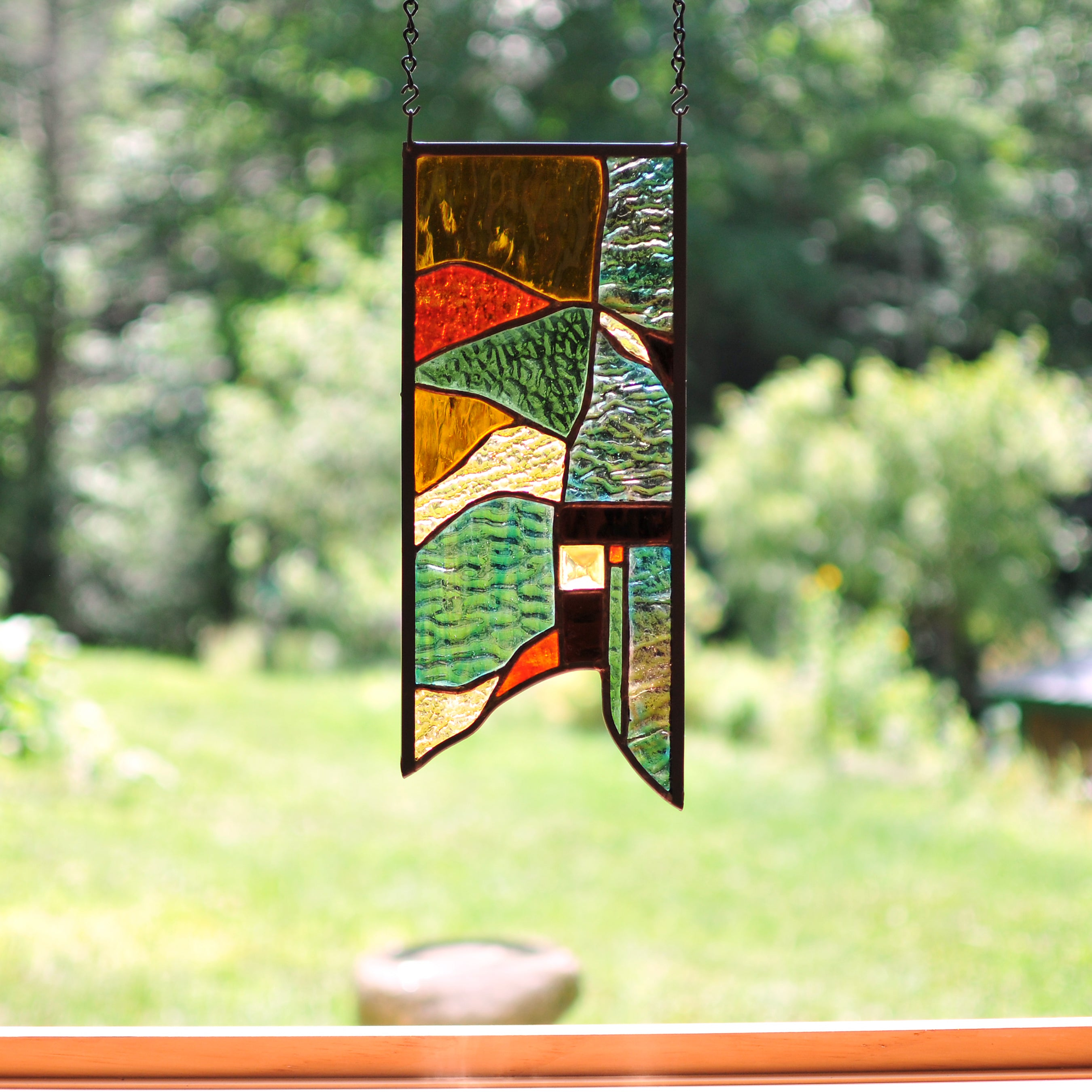 Small stained glass panel with nature inspired organic lines made by Vermont artist Julia Brandis. Organic abstract.