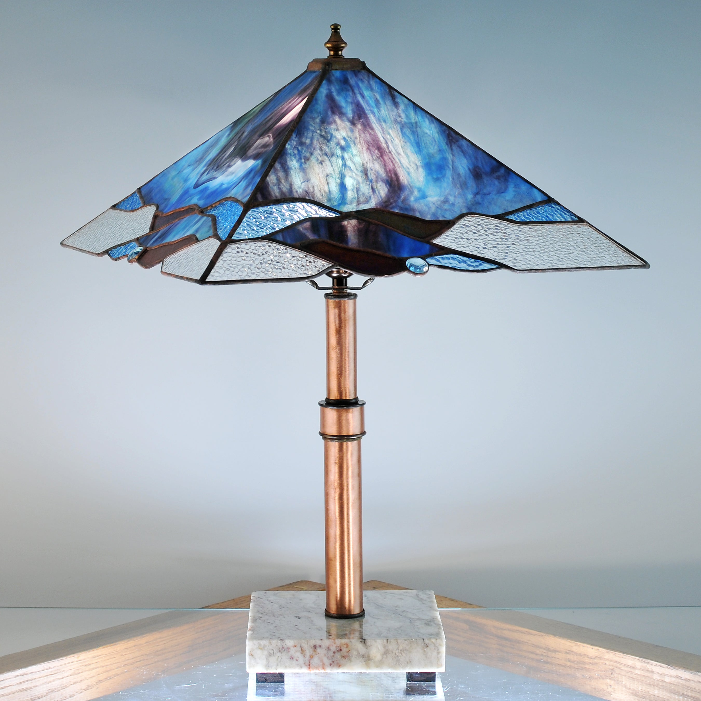 Large stained glass lamp with blue, purple, green and clear swirls made by Vermont artist Julia Brandis. Organic abstract.