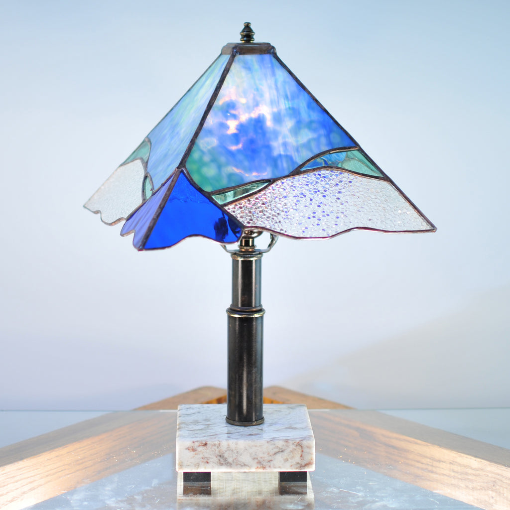 Small stained glass lamp with blue, green and clear organic swirls made by Vermont artist Julia Brandis.