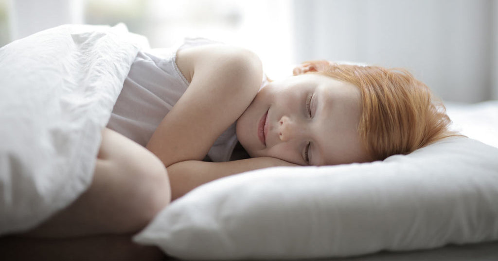 Image contains a photo of a red-haired girl laying in her bed with her head on a pillow. Her eyes are closed and her knee is visible just above the blanket on top of her.