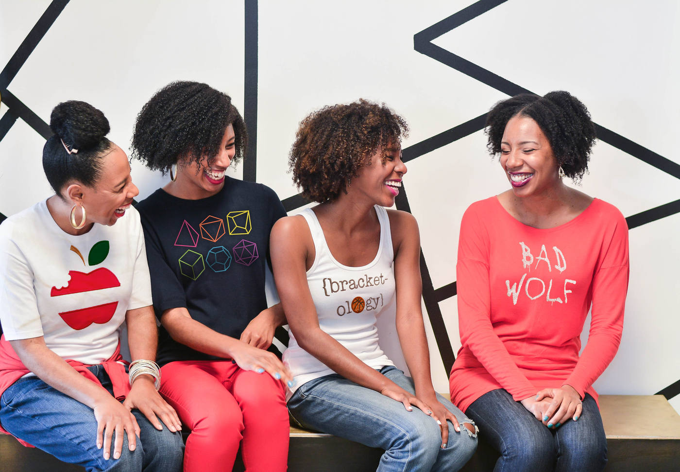 Four black women are sitting on a bench in front of a white wall with geometric black artwork. The women are smiling and laughing. Each woman has a shirt with an applique or embroidery design on the front.