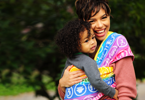 A multiracial woman is smiling while wearing her multiracial toddler in a woven fabric baby carrier. The woven wrap features white inclusive symbols on a background of rainbow colored stripes. They are outside and greenery is visible in the background.