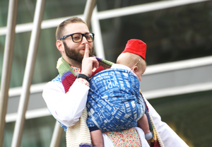 A bearded white man in glasses is cosplayed as Osgood from Doctor Who, wearing a lab coat, floral shirt, bow tie, and striped scarf. He wears a white infant in a blue woven fabric baby wrap with white words and symbols. The baby has a red fez.