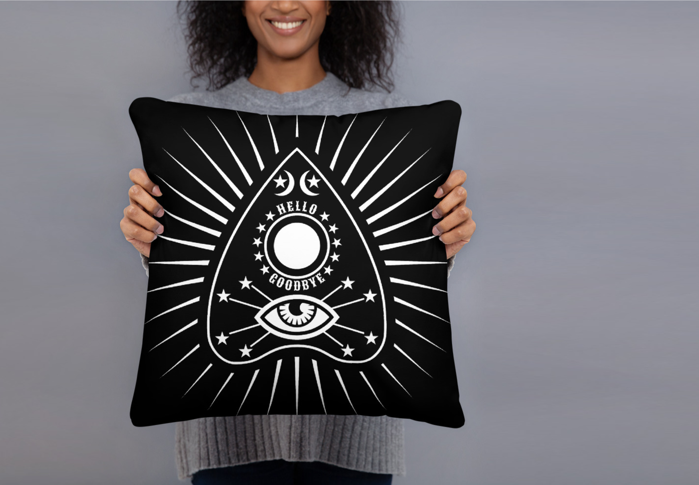 A smiling black woman holds a throw pillow in front of her. The pillow is black with a white communication board planchette design with lines radiating out from it. She stands against a grey wall.