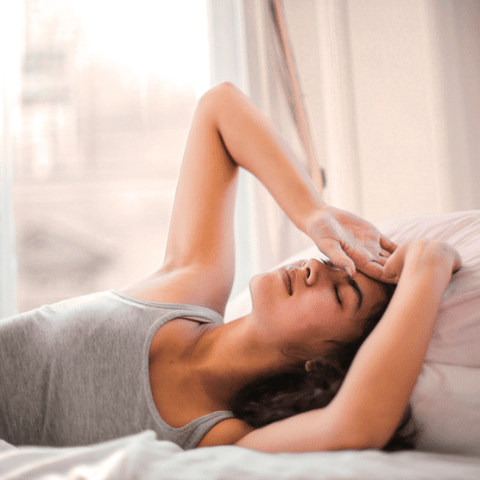 Are candles bad for you?  Woman laying on bed while holding her head and appearing to be in pain