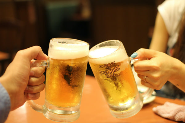 Two persons holding glass beer mugs