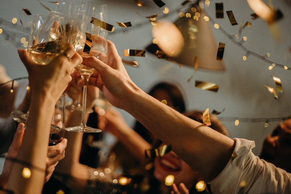 People toasting wine glasses at a party