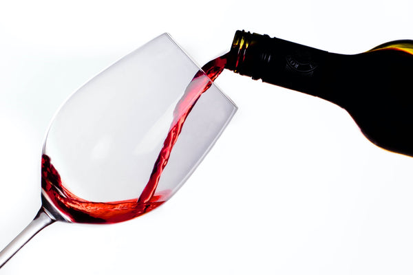 A bottle pouring red wine in a glass