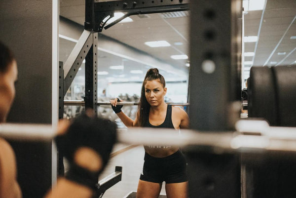 A fit woman is looking in the mirror while lifting a heavy weight at the squat rack in a gym.