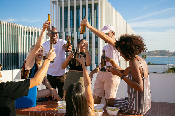 Seven friends are joyfully toasting with beer on a rooftop
