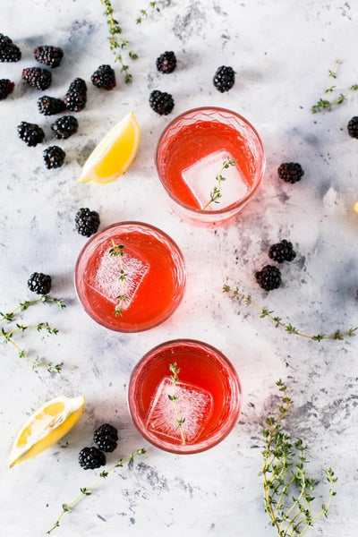 Fruity pink cocktails lying on a marble counter.