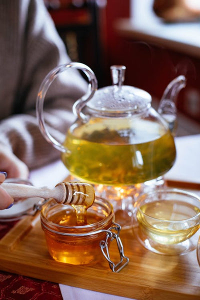 Honey is shown with herbal tea and a cup all on a wooden tray.
