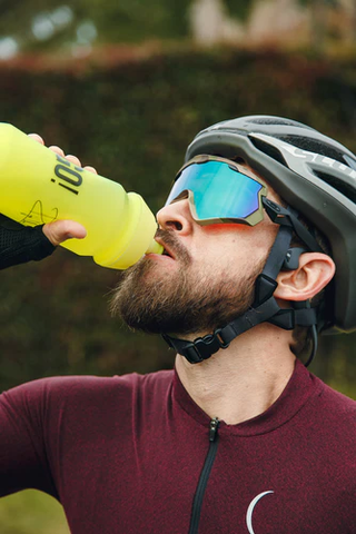 Man consuming electrolyte drink after cycling