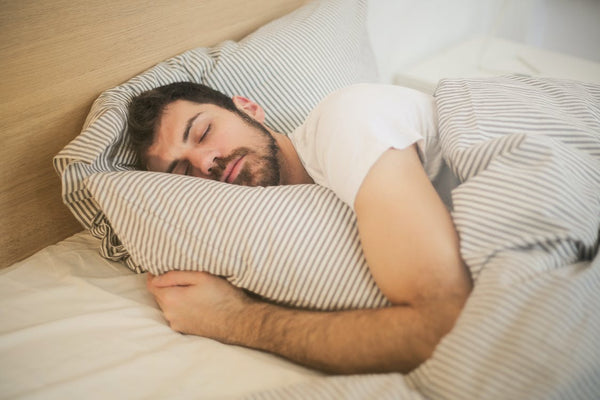 A man is fast asleep in his bed after drinking his advanced hydration electrolyte supplement.